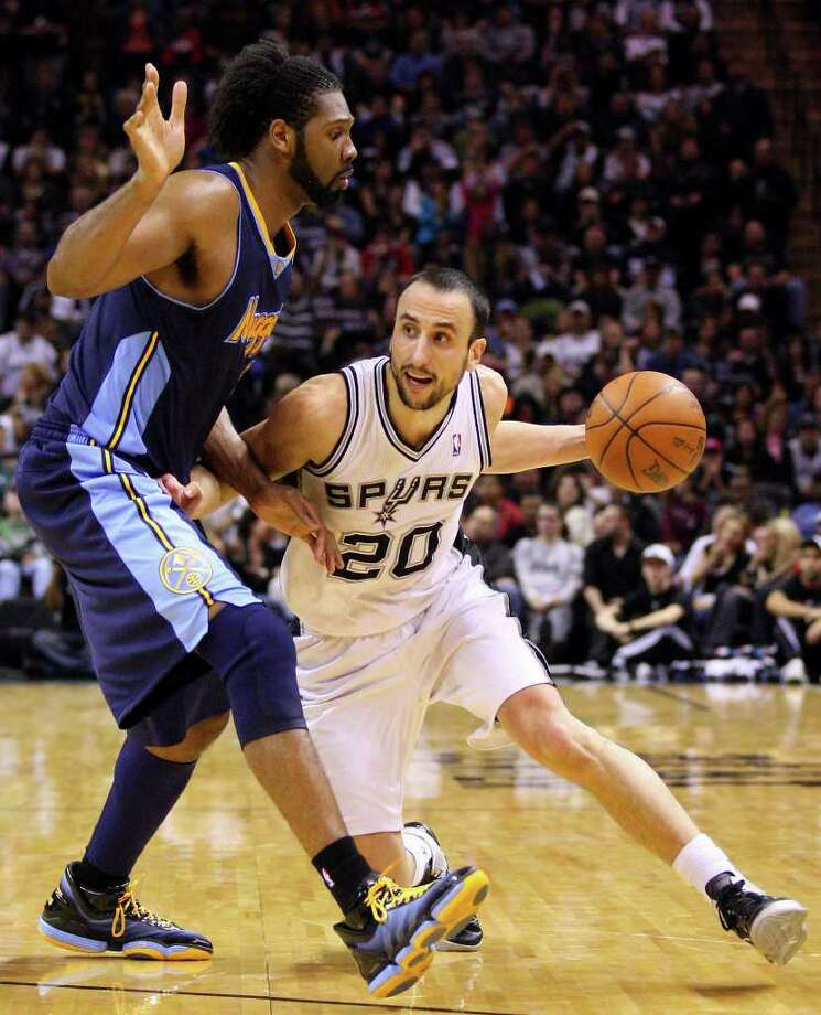 FOR SPORTS - Spurs' Manu Ginobili looks for room around  Nuggets' Nene during second half action Sunday Jan. 16, 2011 at the AT&T Center. The Spurs won 110-97. Photo: EDWARD A. ORNELAS, SAN ANTONIO EXPRESS-NEWS / eaornelas@express-news.net