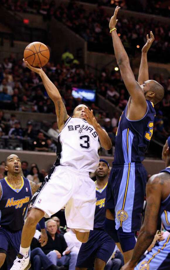 FOR SPORTS - Spurs' George Hill shoots between  Nuggets defenders during second half action Sunday Jan. 16, 2011 at the AT&T Center. The Spurs won 110-97. Photo: EDWARD A. ORNELAS, SAN ANTONIO EXPRESS-NEWS / eaornelas@express-news.net