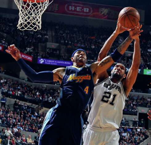 FOR SPORTS - Spurs' Tim Duncan and Nuggets' Kenyon Martin grab for a rebound during second half action Sunday Jan. 16, 2011 at the AT&T Center. The Spurs won 110-97. Photo: EDWARD A. ORNELAS, SAN ANTONIO EXPRESS-NEWS / eaornelas@express-news.net