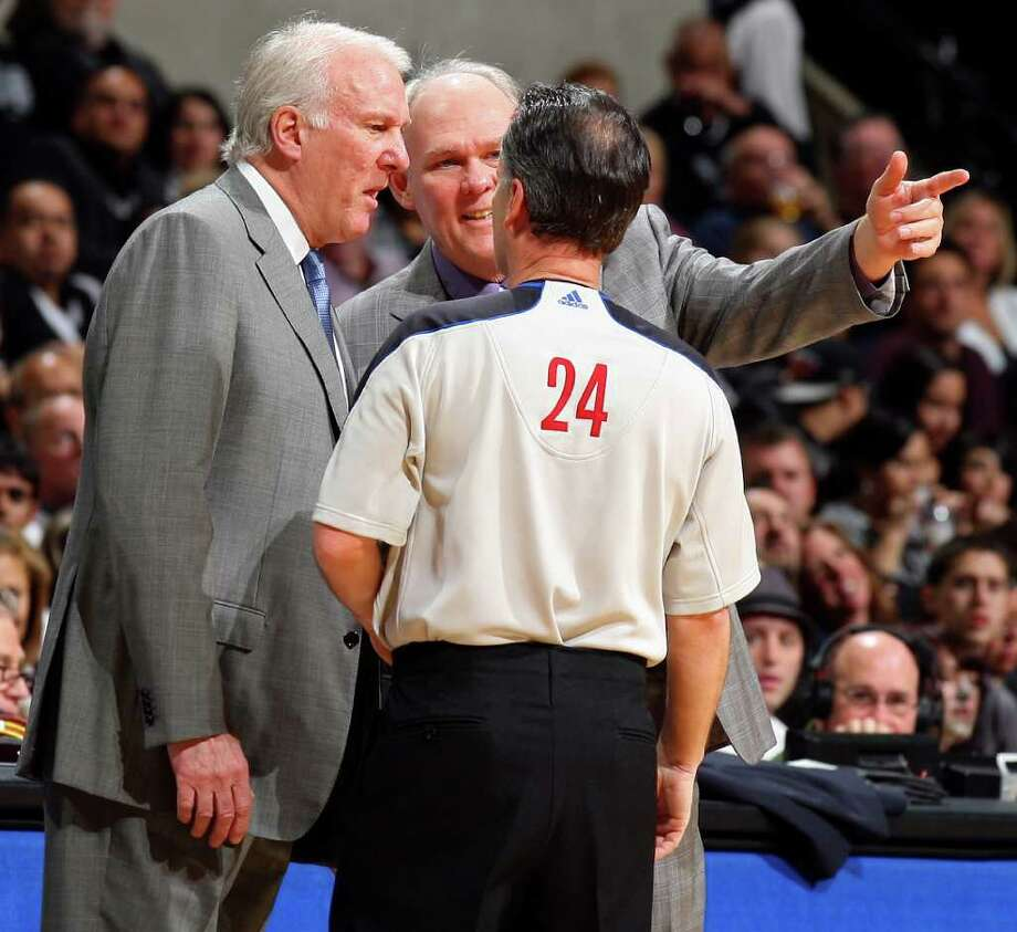 FOR SPORTS - Spurs head coach Gregg Popovich and Nuggets head coach George Karl talk with official Mike Callahan during first half action Sunday Jan. 16, 2011 at the AT&T Center. Photo: EDWARD A. ORNELAS, SAN ANTONIO EXPRESS-NEWS / eaornelas@express-news.net