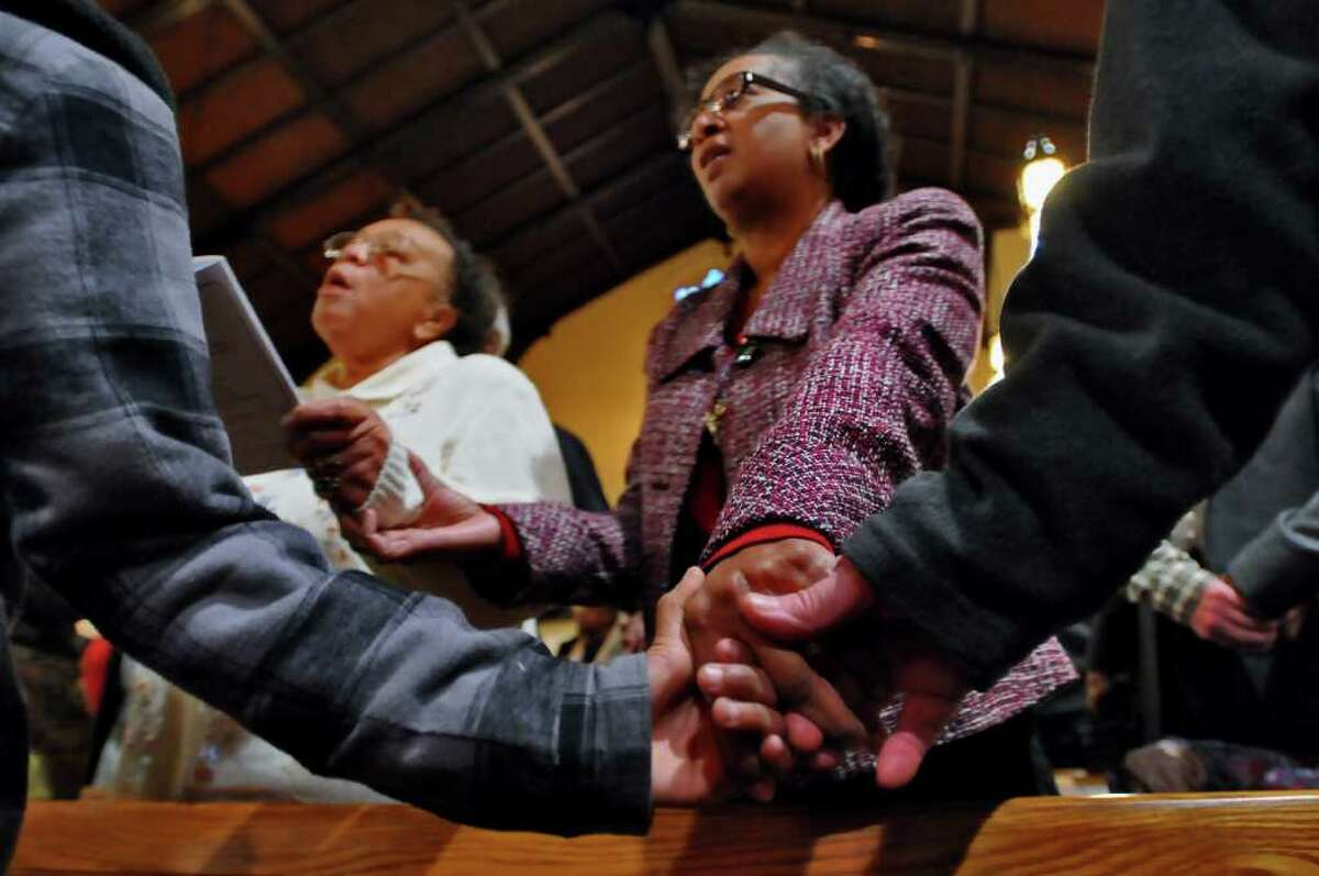 Mildred Mason, upper left, holds hands with Desiree Chaires, right, and the hands of Malachi Warner, 9, and Gregg Millett, right, while singing