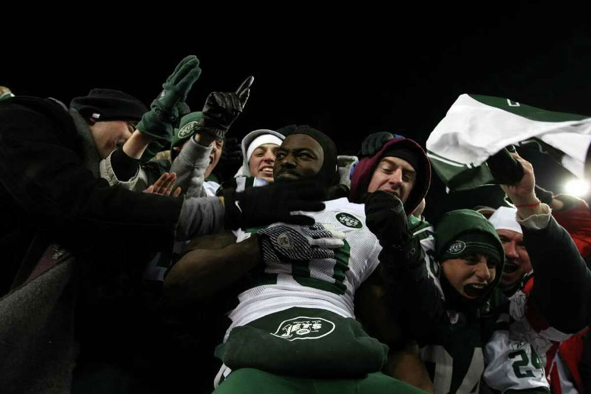 FOXBORO, MA - JANUARY 16: Santonio Holmes #10 of the New York Jets celebrates with fans after the Jets defeated the Patriots 28 to 21 in their 2011 AFC divisional playoff game at Gillette Stadium on January 16, 2011 in Foxboro, Massachusetts. (Photo by Al Bello/Getty Images) *** Local Caption *** Santonio Holmes