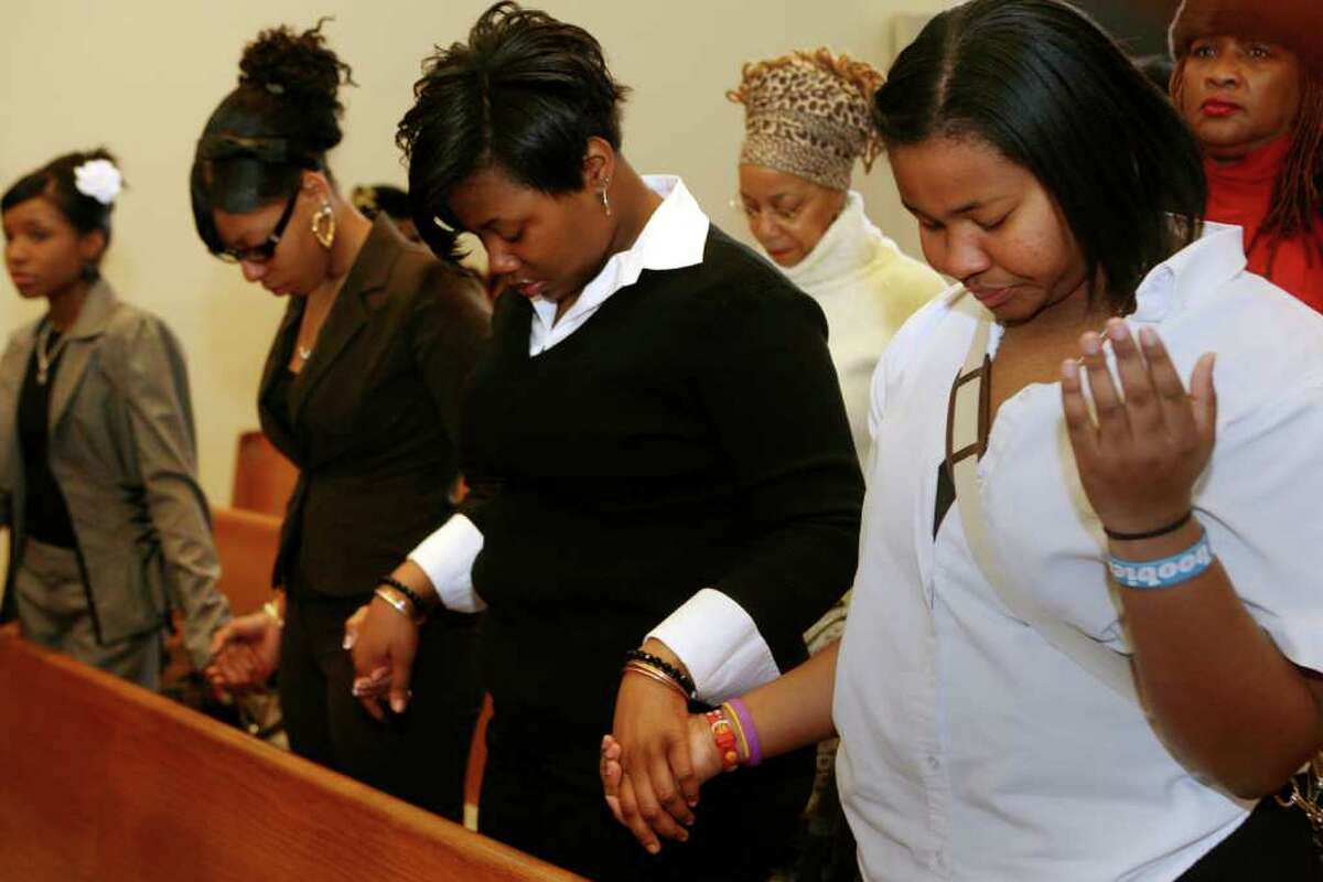 Members of Bridgeport's Black Pride NSBE, from left, Monique Wilson, Donisha Vinson, Jazmin Jean Baptiste, and Shanice Maxwell, pray during the 32nd Annual Dr. Martin Luther King, Jr. celebration at Mount Avery Baptist Church in Bridgeport on Monday, Jan. 17, 2011.