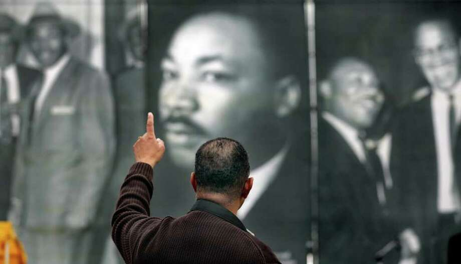 Tony Logan, listening to the music of  O.S. Grant, raises his hand in front of historic photographs on a banner behind the stage at the MLK Early Worship Program as the 24th City of San Antonio Martin Luther King. Jr. Commemorative March made it's way to Pittman Sullivan Park, Monday, Jan. 17, 2011. photo Bob Owen/rowen@express-news.net Photo: BOB OWEN, SAN ANTONIO EXPRESS-NEWS / SAN ANTONIO EXPRESS-NEWS