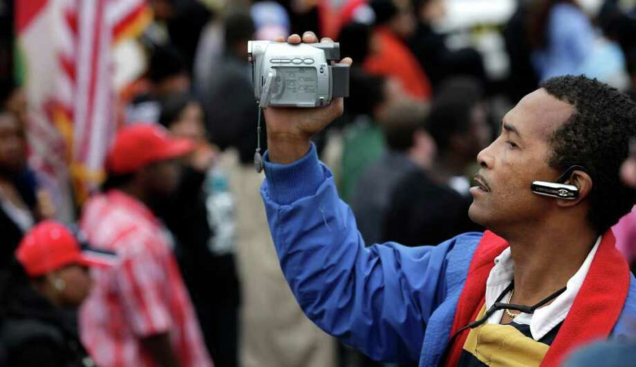 Tommie Nalls III videotapes the 24th City of San Antonio Martin Luther King. Jr. Commemorative March as it enters Pittman Sullivan Park, Monday, Jan. 17, 2011. photo Bob Owen/rowen@express-news.net Photo: BOB OWEN, SAN ANTONIO EXPRESS-NEWS / SAN ANTONIO EXPRESS-NEWS