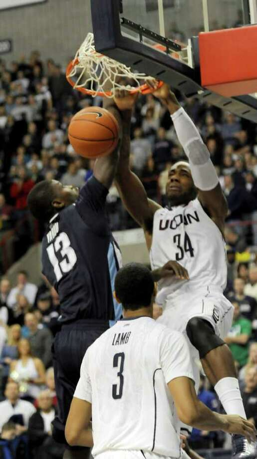 Connecticut's Alex Oriakhi dunks the ball as Villanova's Mouphtaou Yarou of Benin tries to stop him in the first half of an  NCAA men's college basketball game at Storrs, Conn., Monday, Jan. 17, 2011.   Watching is Connecticut's Jeremy Lamb.  (AP Photo/Bob Child) Photo: AP
