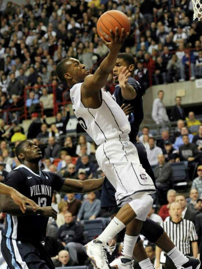 Connecticut's Ke,mba Walker goes up for a shot past Villanova's Russell Wooten in the first half of an  NCAA men's college basketball game at Storrs, Conn., Monday, Jan. 17, 2011.     (AP Photo/Bob Child) Photo: AP