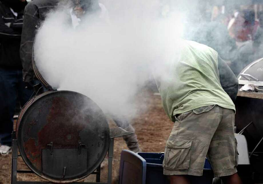 Metro daily - Jerry Hill tends to his grill at Pittman Sullivan Park after the 24th City of San Antonio Martin Luther King. Jr. Commemorative March, Monday, Jan. 17, 2011. photo Bob Owen/rowen@express-news.net Photo: BOB OWEN, SAN ANTONIO EXPRESS-NEWS / SAN ANTONIO EXPRESS-NEWS