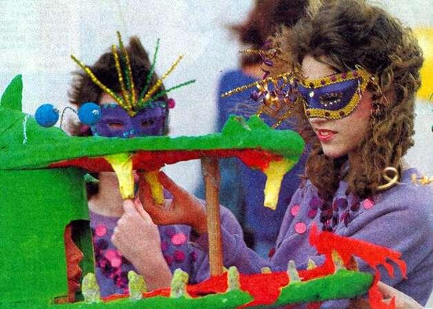 """Kristen Gaines, 14, checks the teeth of a dragon's head worn by Thad McKinley, 12, Saturday in Beaumont."" Enterprise file photo Feb. 1986"
