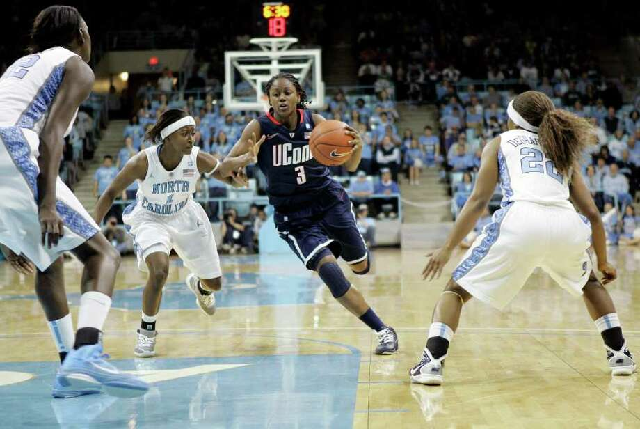 Connecticut guard Tiffany Hayes (3) drives to the basket past North Carolina's She'la White (1),center, Waltiea Rolle (32), left, and Cetera DeGraffenreid (22) during the first half of an NCAA college basketball game in Chapel Hill, N.C., Monday, Jan. 17, 2011. (AP Photo/Jim R. Bounds) Photo: AP