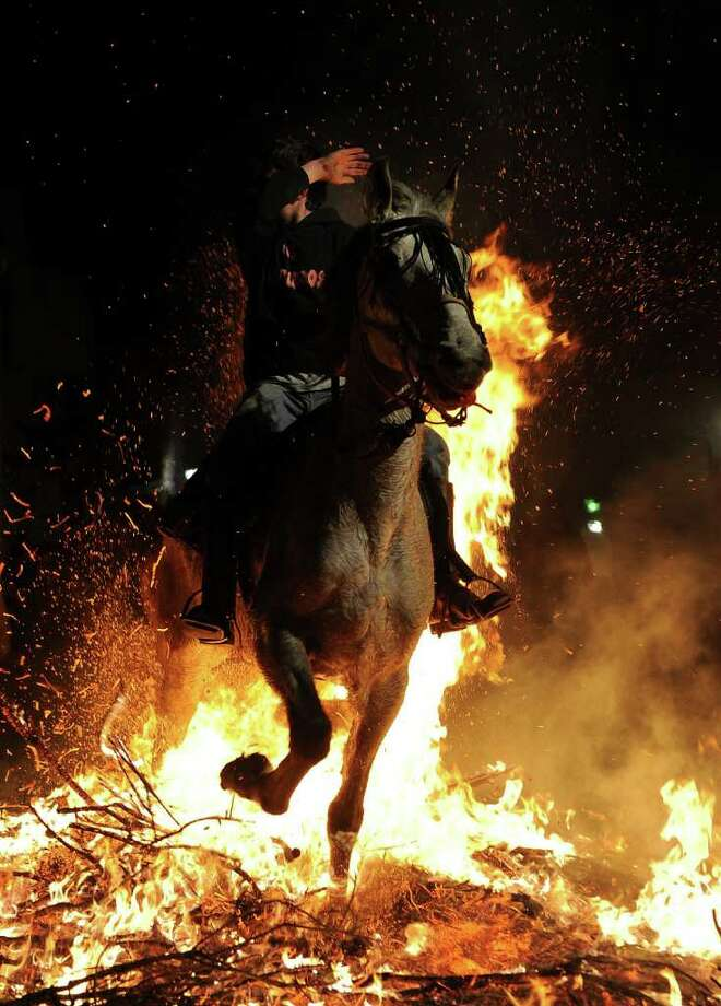 SAN BARTOLOME DE PINARES, SPAIN - JANUARY 16:  A boy covers his face from the flames as he rides a horse through a bonfire on January 16, 2011 in the small village of San Bartolome de Pinares, Spain. In honor of San Anton, the patron saint of animals, horses are riden through the bonfires on the night before the official day of honoring animals in Spain.  (Photo by Jasper Juinen/Getty Images) Photo: Jasper Juinen, Getty Images / 2011 Getty Images