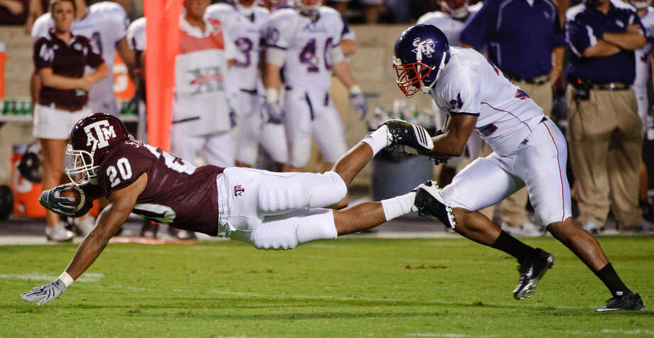 Texas A&M's Bradley Stephens, seen here diving past Stephen F. Austin's Delano King for a first down during a Sept. 4 game, opted to forego his last season of eligibility to graduate and enter the workforce. Stephens rushed for 328 yards the last three seasons. Photo: Associated Press File Photo