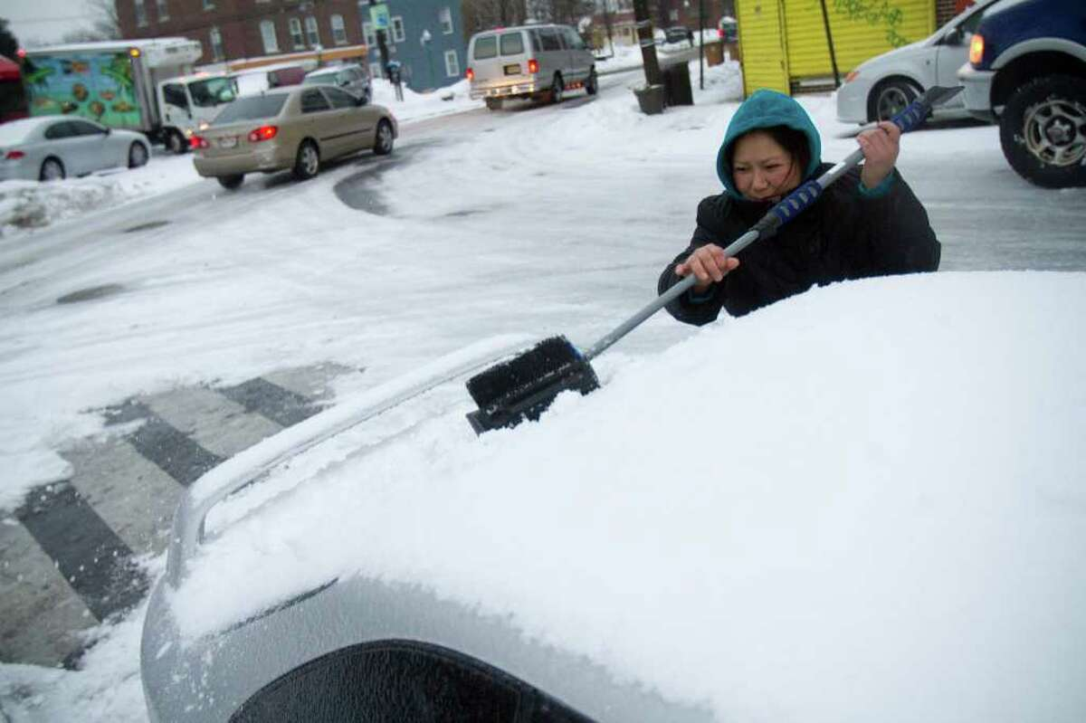 Maura Castro sweeps snow off of her car during a snow and ice storm in Stamford, Conn. on Tuesday, Jan. 18, 2011.