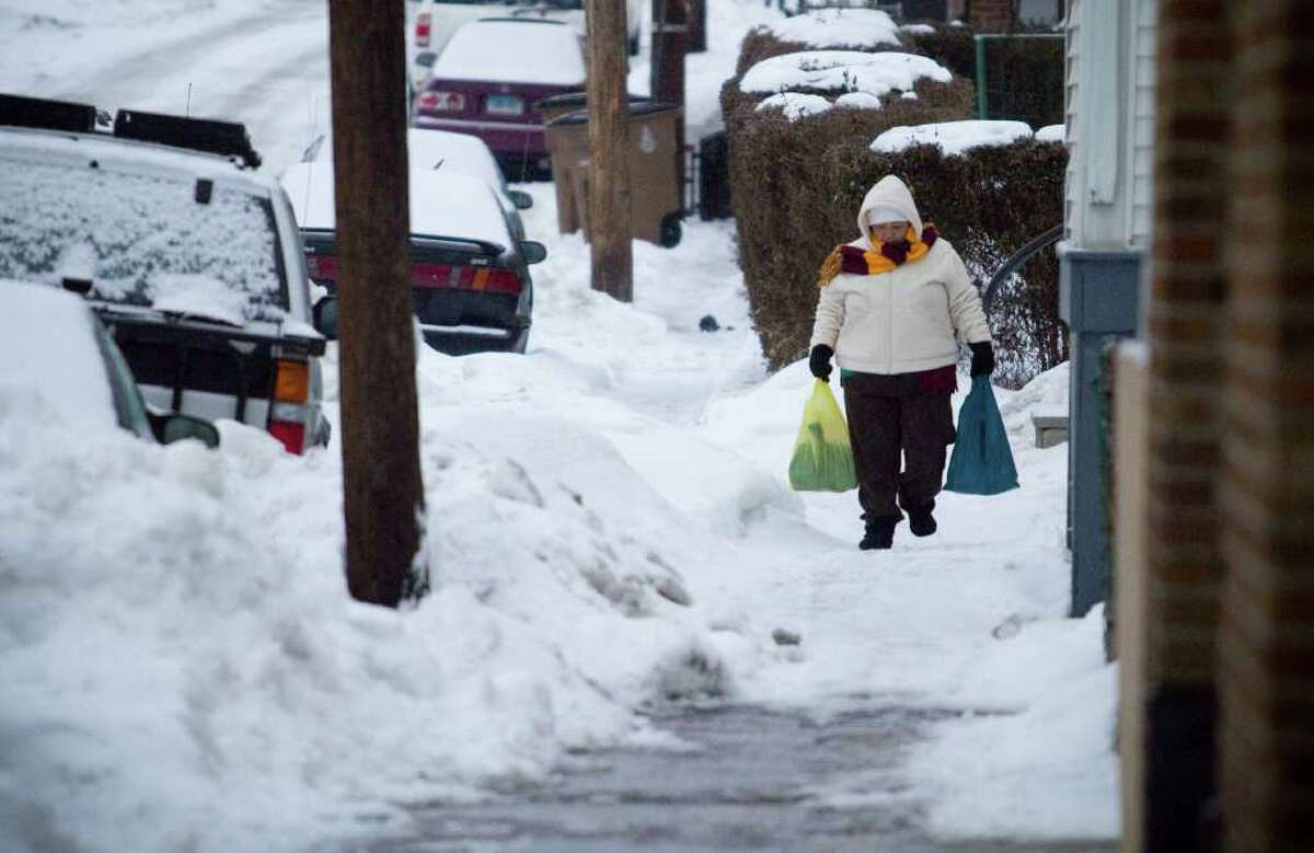 A woman walks down Stephen Street during a snow and ice storm in Stamford, Conn. on Tuesday, Jan. 18, 2011.