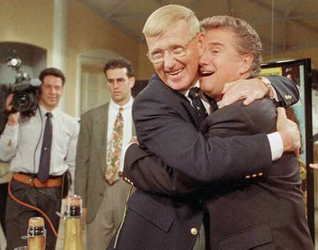 "FILE - In this May 15, 1992, file photo, talk-show host Regis Philbin gets a hug from Notre Dame football coach Lou Holtz during  a live broadcast of ABC's ""Live With Regis and Kathy Lee,""  in New York. The seeming ageless morning show host might love the Fighting Irish more than his co-host, Kelly Ripa. Current Notre Dame coach Brian Kelly was in the show earlier this year and former Fighting Irish coaches lou Holtz, Tyrone Willingham and Charlie Weis have also been guests. (AP Photo/Steve Freeman, File) Photo: Steve Freeman, STR"