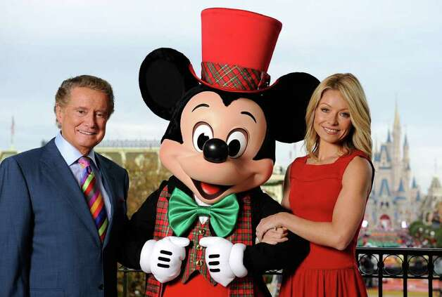 """In this photo released by Disney, Regis Philbin, left, and Kelly Ripa pose with a holiday-clad Mickey Mouse, Saturday, Dec. 6, 2008 at the Magic Kingdom in Lake Buena Vista, Fla., while taping the """"Walt Disney World Christmas Day Parade,"""" to be aired nationwide Dec. 25 on ABC-TV.  Special guest performers include Miley Cyrus, Billy Ray Cyrus, Jose Feliciano, Corbin Bleu, the Jonas Brothers, David Cook, the Imagination Movers and Sarah Brightman. Philbin and Ripa once again host the Christmas special, which marks its 25th anniversary this year. (AP Photo/Disney, Mark Ashman) Photo: Mark Ashman, HO / AP2008"""
