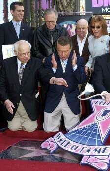 Talk show host Regis Philbin, bottom center, reacts as honorary Mayor of Hollywood Johnny Grant, lower left, presents a star to him on the Hollywood Walk of Fame Thursday, April 10, 2003, in Los Angeles. Watching Philbin are Los Angeles City Councilman Eric Garcetti, top left, talk show host Larry King, second left, comedian Don Rickles and Philbin's wife Joy, top right. (AP Photo/Nick Ut) Photo: NICK UT, STF / AP2003