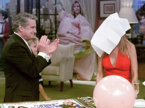 "Regis Philbin, left, applauds as co-host Kathie Lee Gifford covers her face with a napkin at the end of her last show, in New York Friday July 28, 2000. After 15 years of chatter, camaraderie and controversy, Gifford bid farewell Friday to Philbin and their morning talk show, ""Live with Regis & Kathie Lee."" With tears in her eyes, Gifford stood next to Philbin and mouthed ""thank you"" to the audience, then covered her face with a white napkin. (AP Photo/Richard Drew) Photo: RICHARD DREW, STF / AP2000"