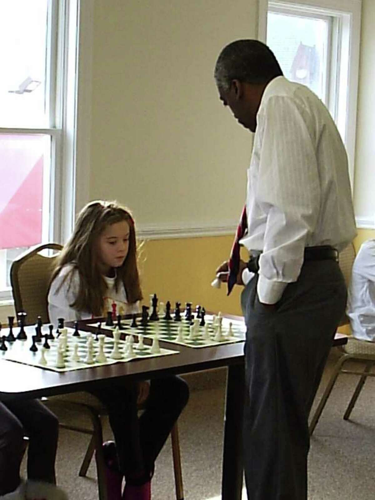 Melvin Patrick plays a game of chess with a child at the club.