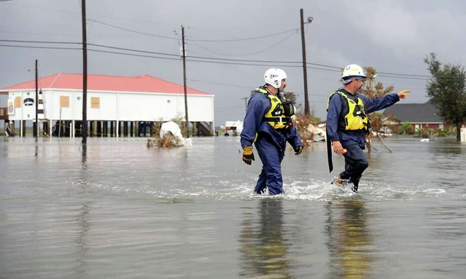 Rescue  workers  search for residents  in   Sabine Pass, Sunday. Tammy McKinley/ Photo: THE ENTERPRISE