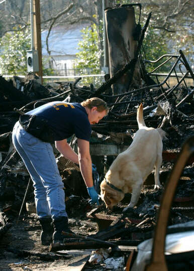 An ATF special agent works with an arson dog during an investigation of fatal trailer fire in Newton