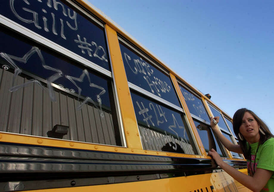 Woodville Cheerleader Laura Garess waits for the spelling of another name for a bus window. Photo: Dave Ryan