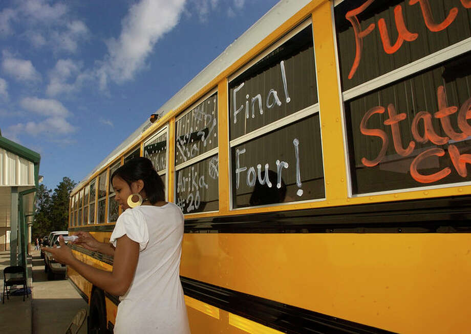 Woodville Cheerleader Ashley Mitchell grabs another color for another  bus window. Photo: Dave Ryan