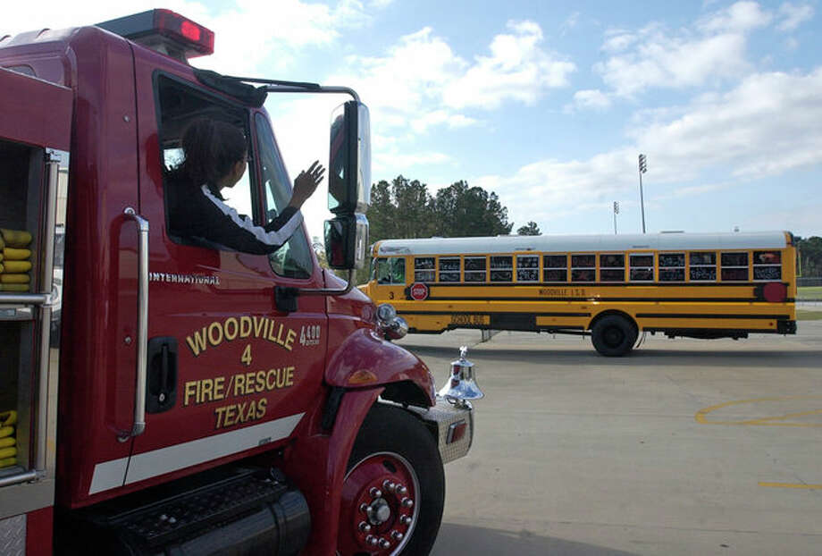 The Woodville girls basketball team bus is decorated and headed to Austin as the  Woodville Fire department escorts them out of town. Photo: Dave Ryan