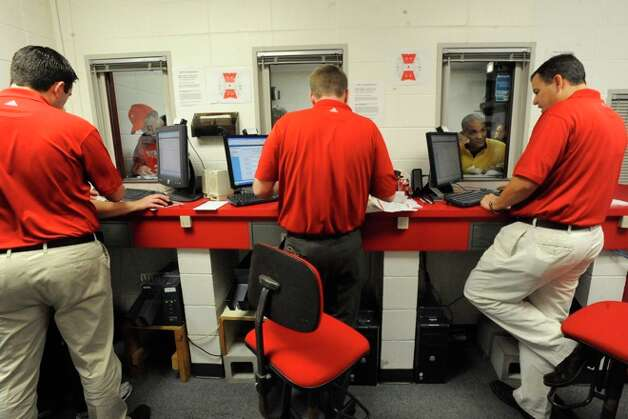 Lamar Athletics officials help the first set of customers choose seats for Lamar Football season tickets. Lamar University began selling season tickets at 7 a.m. on Saturday, with some Lamar fans lining up overnight to be the first in line for good seats. Saturday, January 23, 2010. Photo: VALENTINO MAURICIO