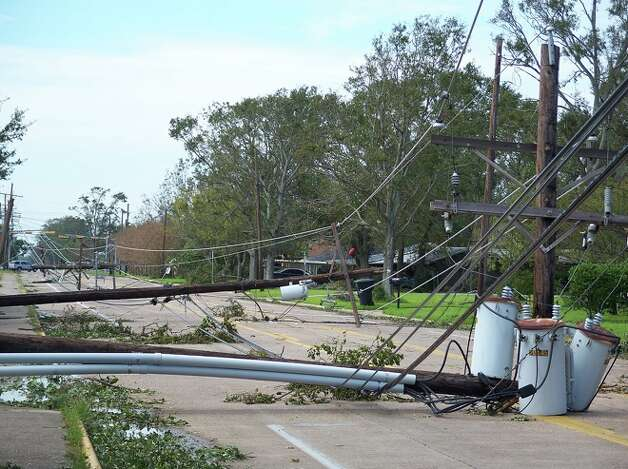 Power poles and lines lay along Avenue H in front of Doornbos Park in Nederland on Monday. Tammie Hodges/ Photo: THE ENTERPRISE