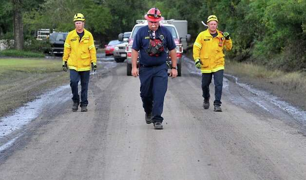Coppell Fire Department's Ty Richardson, Mark Elliott, and Robert Ridling walk along Fishhook Lane doing search and rescue operations and disabling electrical lines in Bridge City, Monday. Tammy McKinley/ Photo: THE ENTERPRISE