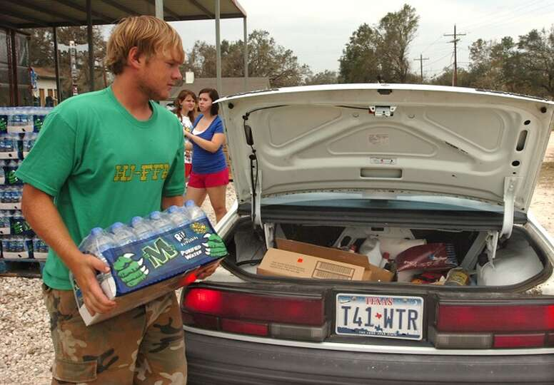 17-year-old Justin Floyd of Sour Lake loads bottled water into a car at the all-volunteer Catholic C