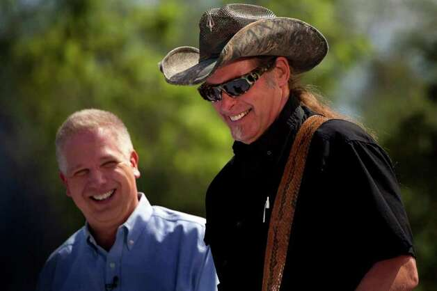 Glenn Beck, left, looks on as Ted Nugent performs at  Alamo Plaza for a Tea Party Wednesday, April 15, 2009.  There were protests nationwide to rally against excessive government spending. NICOLE FRUGE/nfruge@express-news.net Photo: NICOLE FRUGE, SAN ANTONIO EXPRESS-NEWS / nfruge@express-news.net