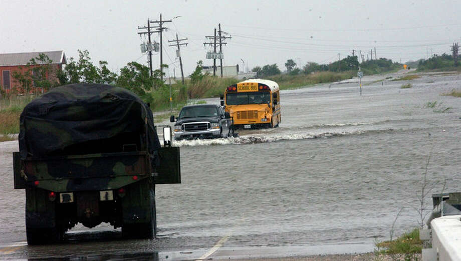 A school bus follows a 4 wheel drive truck through the waters covering Texas 87 to Sabine Pass Friday morning.  Dave Ryan/ Photo: THE ENTERPRISE