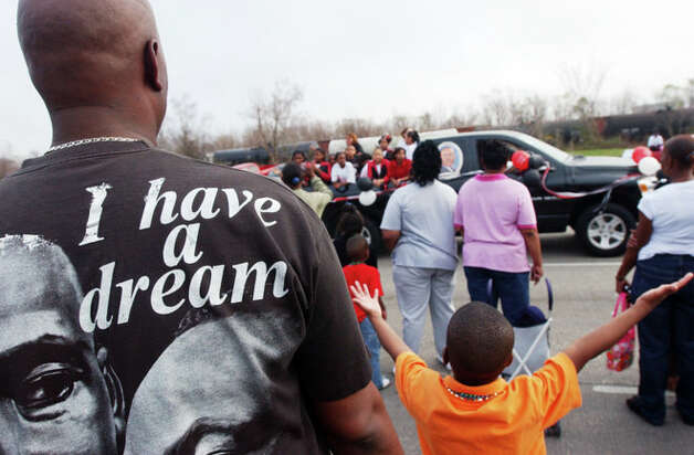 Darryl Eldridge, left, looks on as his nephew Nathaniel, 6, holds his hands high for treats thrown out by participants in a parade honoring Martin Luther King, Jr. Saturday, Jan. 13, 2007, on Martin Luther King Parkway in Beaumont. The parade was in its 20th year. Andrew Nenque/ Photo: THE ENTERPRISE