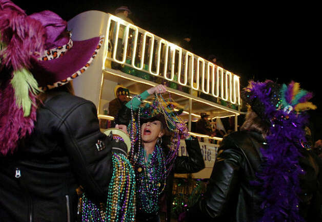Beverly Allen of Nederland (center) shows her beads to friends Charlotte Davis, of Beaumont, left, and Lisa Harper, of Port Neches, in the first-ever Mardi Gras on the Neches parade in Beaumont, Thursday, Feb. 16, 2007.  Mark M. Hancock/ Photo: THE ENTERPRISE