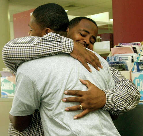 Central High School Offensive Line Coach Eric Jackson, (right), gives Brandon Williams a congratulatory hug.  Central had five of their football players sign to play at schools as their family members watched. Dave Ryan/ Photo: THE ENTERPRISE