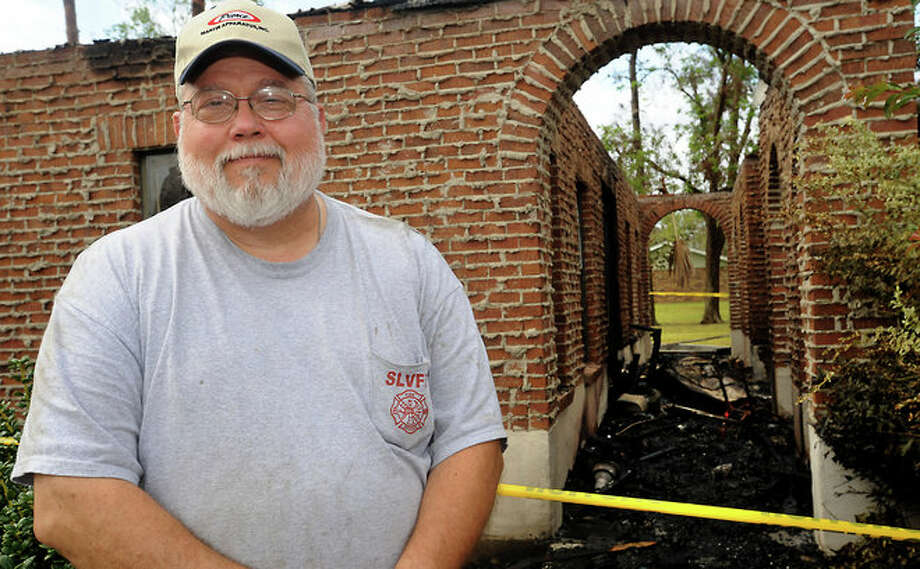 Father Martin Nelson stands near the CCD building at Our Lady of Victory Catholic Church in Sour Lake, Wednesday. The building caught fire as a result of lightning. Photo: TAMMY MCKINLEY