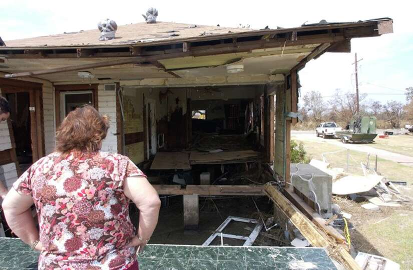 Diane Bergeron, a Sabine Pass resident, looks over the back of her home and the back porch.    Dave