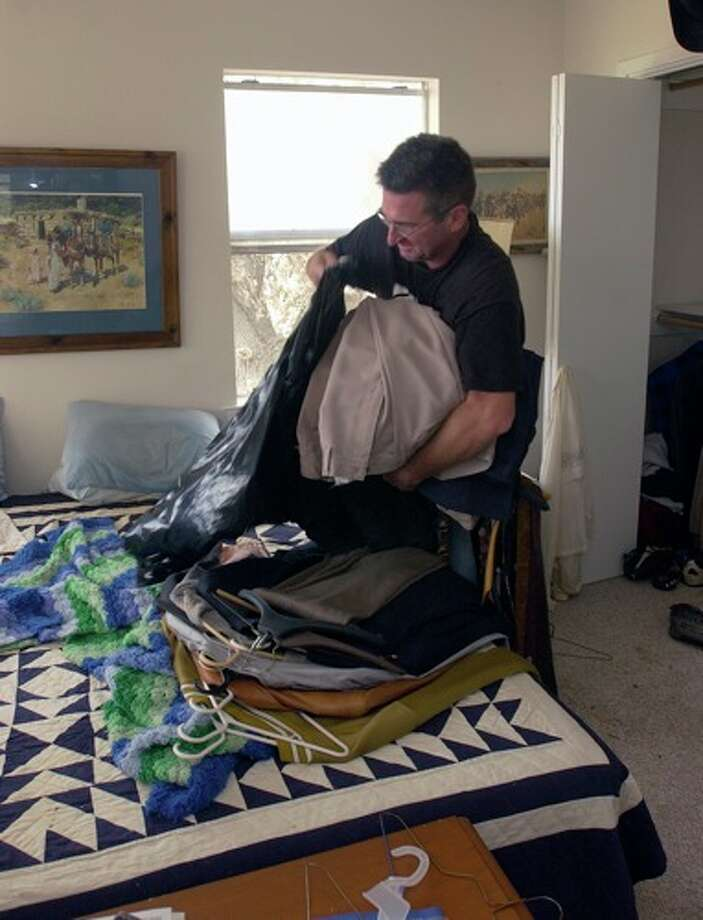Lance Morgan, who's father and uncle live in Sabine Pass, helps pack up his dads possessions from one of the bedrooms.    Dave Ryan/ Photo: THE ENTERPRISE