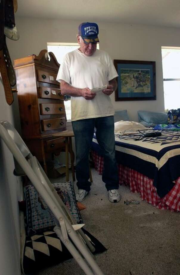 Neil Morgan, a Sabine Pass resident collects undamaged photos as he tries to salvage things from his home.  Dave Ryan/ Photo: THE ENTERPRISE