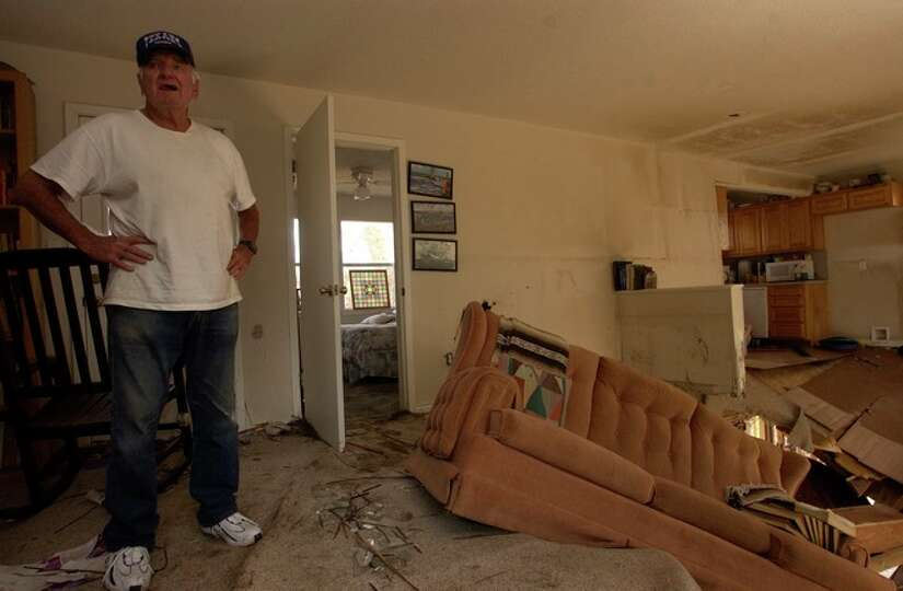 Neil Morgan, a Sabine Pass resident looks over the damage to the home he shares with his brother.  D