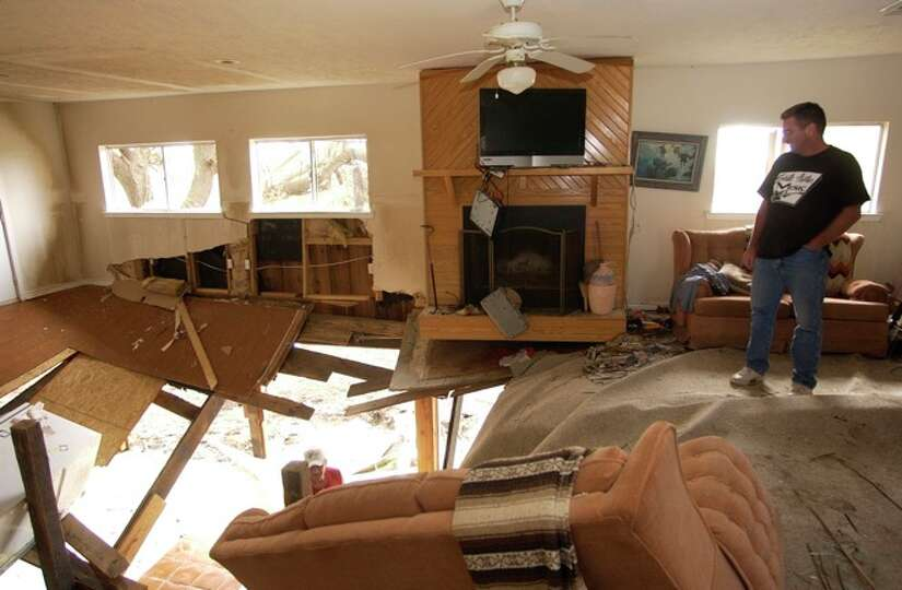 Lance Morgan, who's father and uncle live in Sabine Pass, looks over the damage to the living room o