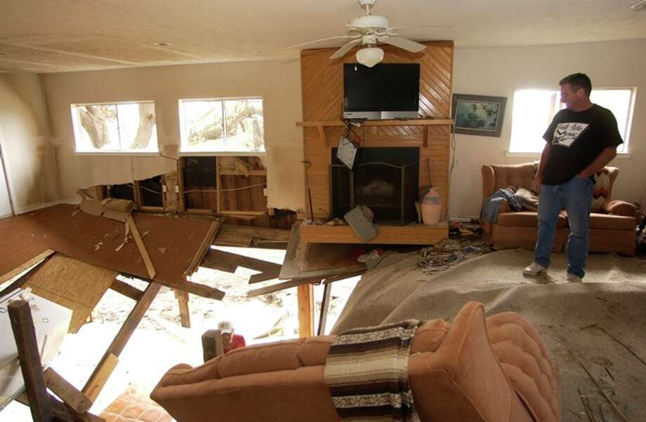 Lance Morgan, who's father and uncle live in Sabine Pass, looks over the damage to the living room of the home.   Dave Ryan/ Photo: THE ENTERPRISE