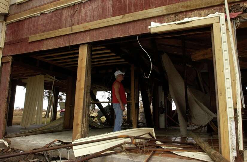 Bob Morgan, a Sabine Pass resident looks over the damage to the home he shares with his brother.  Da
