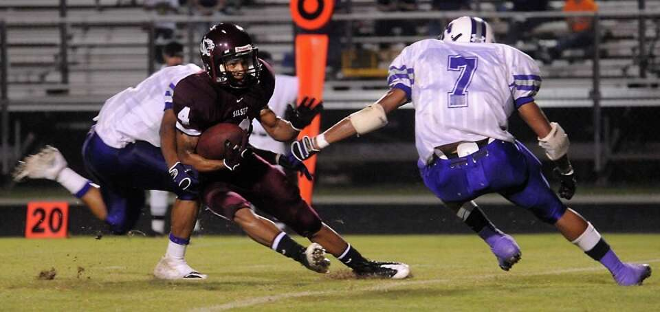 Silsbee's Pheal Hill is brought down by Newton's Delenta Shankle and Brent Spikes at Silsbee High Sc
