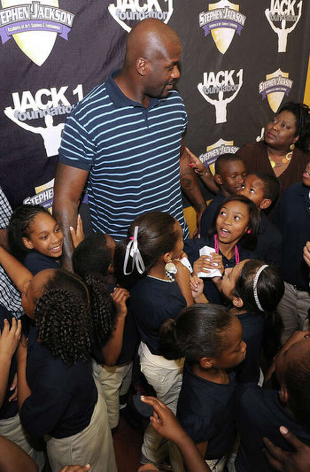 Several youths and adults gather around Shaquille O'Neal at the Stephen Jackson Academy Thursday to take a picture. Photo: Guiseppe Barranco