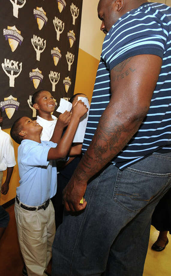 Young boys plead for an autograph from Shaquille O'Neal at the Stephen Jackson Academy on Thursday. Photo: Guiseppe Barranco