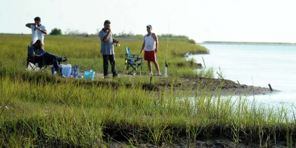 Local residents spend an afternoon fishing from the marshes edge at Keith Lake near Sabine Pass, Sun