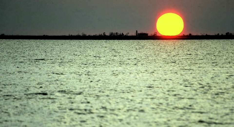 The sun sets over Port Arthur as seen from Sabine Pass, Sunday.